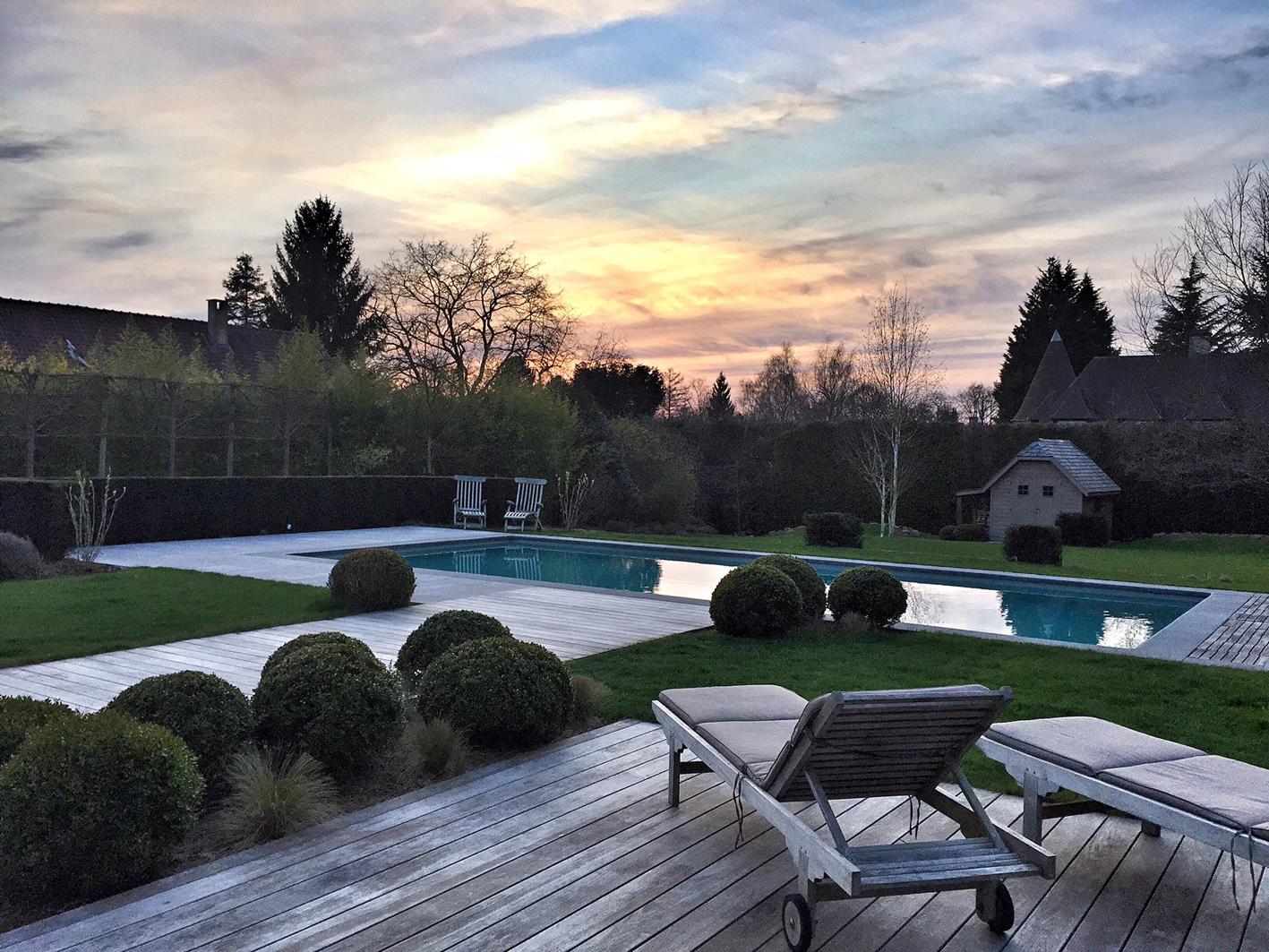 Coucher de soleil sur un espace piscine avec son habillage de terrasses bois et pierre bleue. La touche « cosy » étant apportée par les végétaux proches.