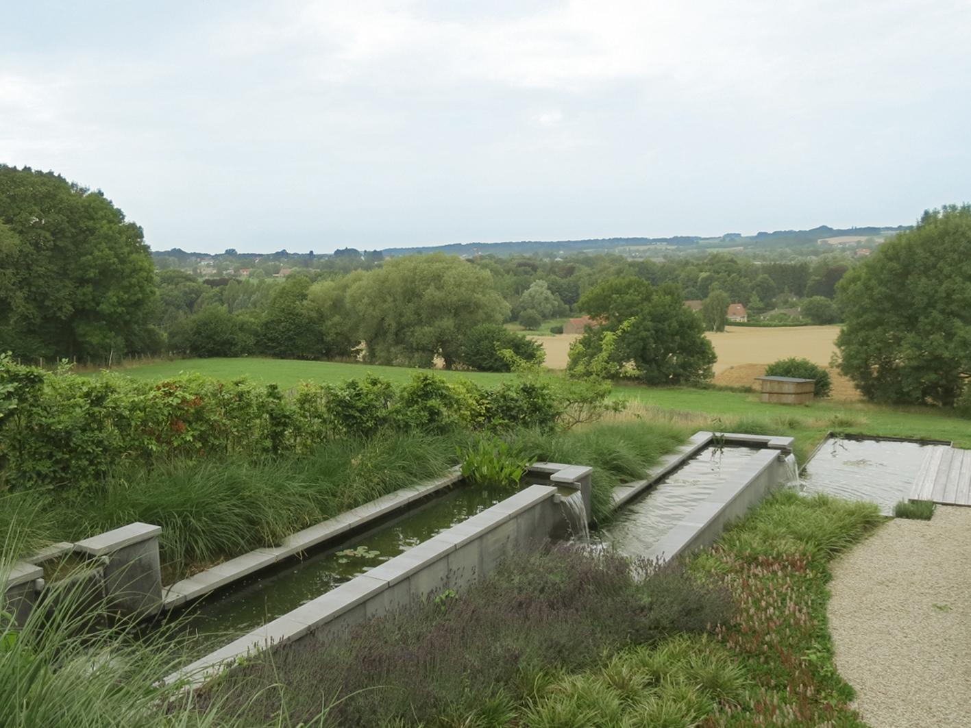 Succession de bassins-canal en cascades servant également de soutènement pour asseoir le talus de terre arrière. Structures maçonnées et parement en pierre bleue belge.